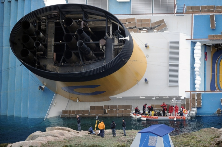<p>Divers on Jan. 19, 2012 prepare for an operation near the Costa Concordia aground in front of the harbor of the Isola del Giglio (Giglio island) after hitting underwater rocks on Jan. 13. Italian rescuers resumed their search on board a crashed cruise ship the same day, as salvage workers prepared to pump out fuel from its tanks to avoid an environmental disaster.</p>