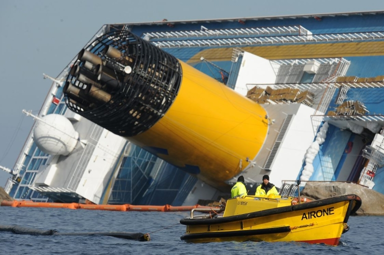 <p>Floating barriers are pulled behind a boat to prevent pollution from the stricken cruise ship Costa Concordia from reaching the coast of the Italian island of Giglio on January 18, 2012.</p>