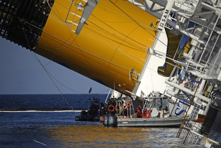 "<p>Technicians work near the stricken cruise liner Costa Concordia, seen lying aground yesterday in front of the Isola del Giglio, or ""Giglio island"" after hitting underwater rocks on Jan 13.</p>"