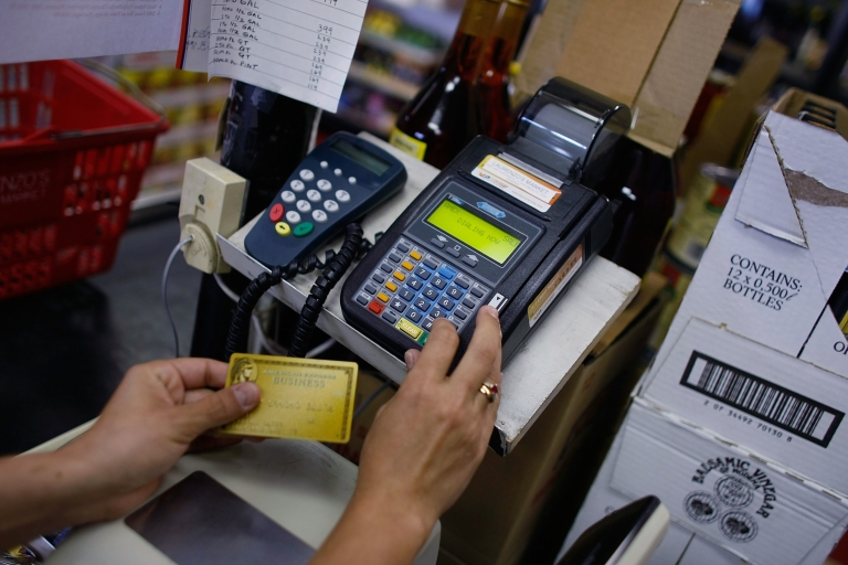 <p>A credit card reader is used to charge a credit card from a customer at Lorenzo's Italian Market in Miami, Fla.</p>