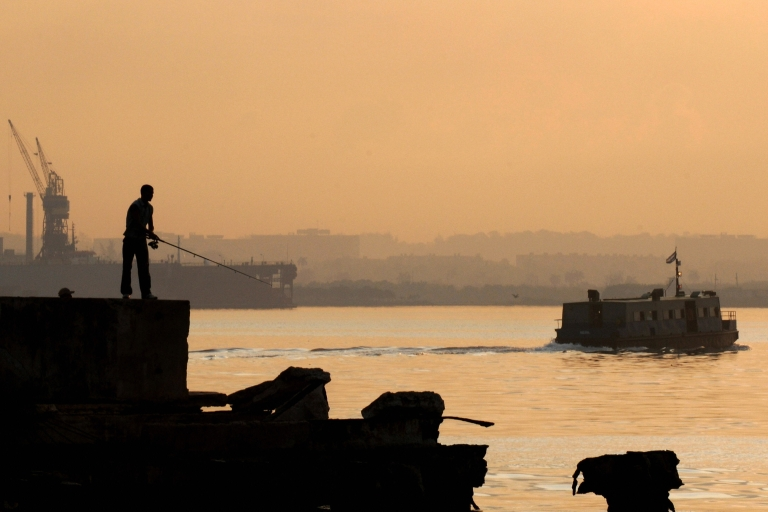 <p>A man fishes in Havana's harbor.</p>