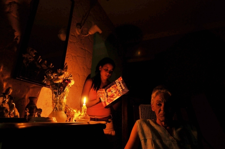 <p>A Cuban girl reads the inscriptions on a food box by candlelight during a power cut on May 31, 2009.</p>
