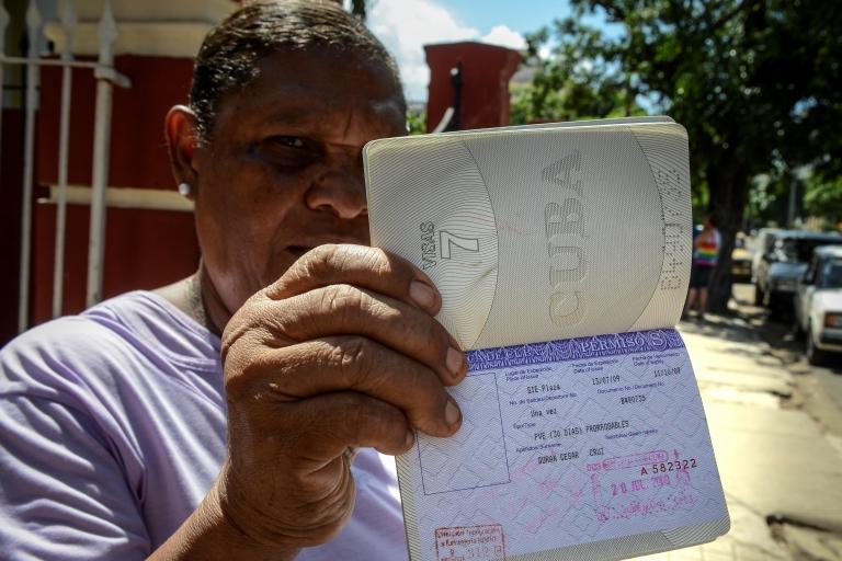 <p>Cuban Cruz Duran shows her passport with a travel permission.</p>