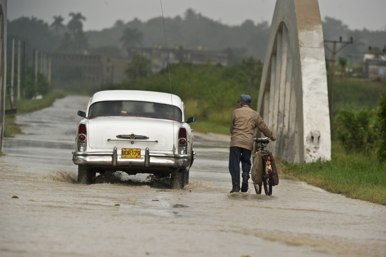 <p>A farmer with his bicycle and a car wade a flooded road, on Oct. 14, 2010, in the municipality of Bahia Honda, 90 km west of Havana, Pinar del Rio province, Cuba, as tropical storm Paula approaches.</p>