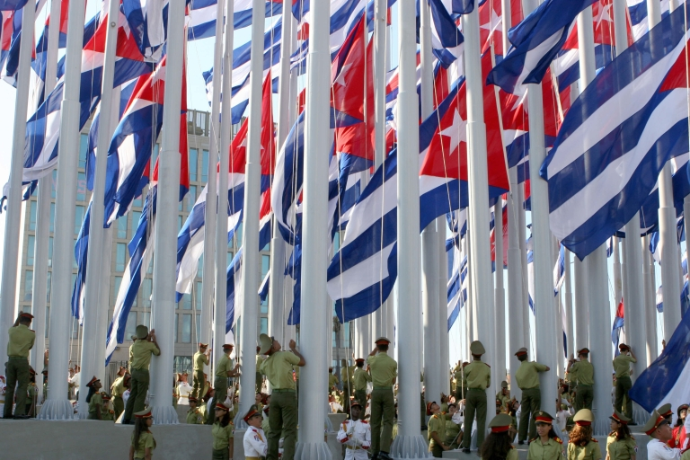 <p>Another red, white and blue: Cuban soldiers hoist Cuban flags in front of the US Interests Office in Havana.</p>