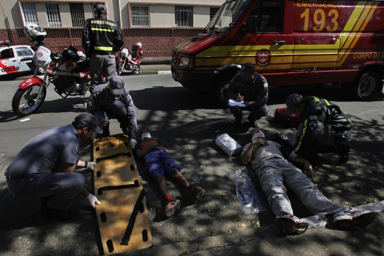 <p>Members of a fireman's rescue brigade prepare a couple of young boys for evacuation after they suffered a bicycle accident near a checkpoint in downtown São Paulo, Brazil, May 19, 2006.</p>