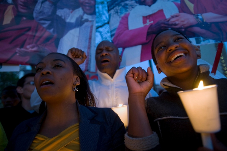 <p>Some 150 people sing the National Anthem during an evening vigil outside the South African Parliament, to call on the South African Government to grant the Dalai Lama a visa to attend Archbishop Tutu's 80th birthday party, on October 3, 2011 in Cape Town.</p>