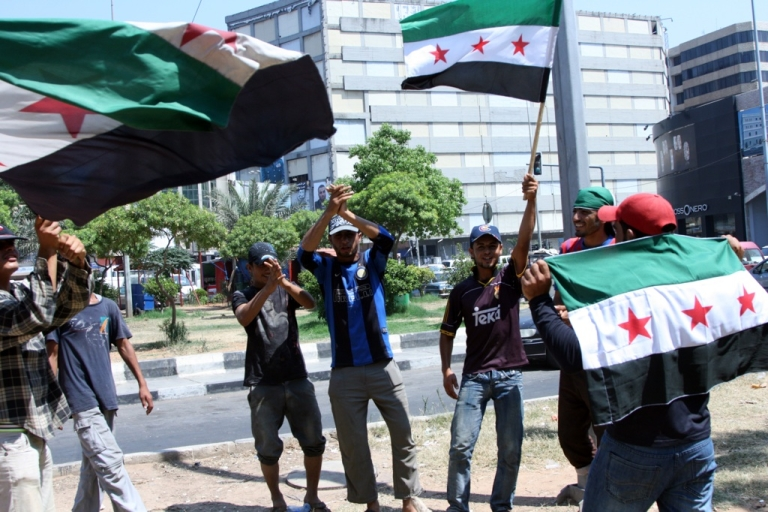 <p>Lebanese men wave pre-Baath flags, that were adopted by the Syrian revolution during the uprising, as they celebrate in the centee of Lebanon's northern town of Tripoli on July 18, 2012, the death of Syrian defense minister General Daoud Rajha in a suicide attack targeting the National Security headquarters in central Damascus.</p>