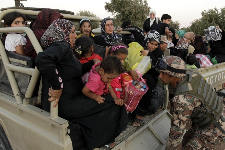 <p>A Jordanian soldier helps newly arrived Syrian refugees after they crossed the border from Syria into Jordan, near the town of Ramtha, on September 5, 2012.</p>