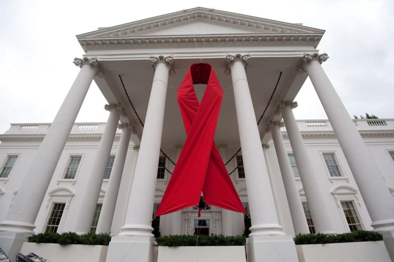 <p>A large red ribbon hangs on the North Portico of the White House in Washington on November 30, 2010.</p>