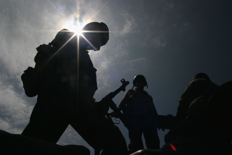 <p>ARROMANCHES, FRANCE - JUNE 5: Military enthusiasts in World War II-era American military gear stand silhouetted against the sun June 5, 2004 at Arromanches, France. Leaders of the former Allied powers and Germany and thousands of veterans will commemorate the D-Day invasion on June 6. (Photo Warrick Page/Getty Images)</p>