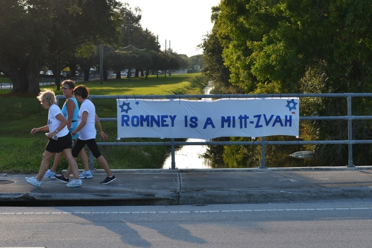 <p>Women walk past a banner claiming US Republican presidential candidate Mitt Romney's support for Israel near Lynn University in Boca Raton, Florida, on Oct. 20, 2012.</p>