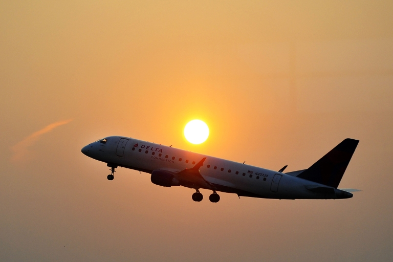 <p>A Delta airline's aircraft takes off from the Ronald Reagan National airport as the sun rises in Washington, DC, on June 9, 2011.</p>