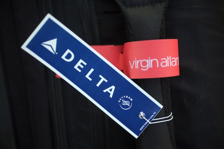 <p>In this photograph illustration a Virgin Airlines and Delta Airlines baggage sit together on the handle of luggage on December 11, 2012 in Manchester, England. Delta Air Lines has agreed to invest $360m (£224m) to buy the 49% stake of Singapore Airlines in Virgin Atlantic. The airlines hope the new joint venture will create an expanded trans-Atlantic network.</p>