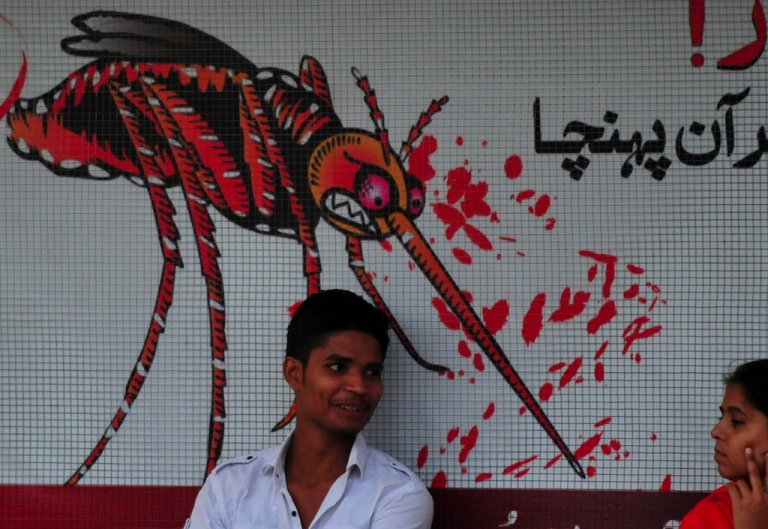 <p>A Pakistani man sits in front of awareness advertisement against the dengue fever, a deadly tropical disease, in Islamabad</p>