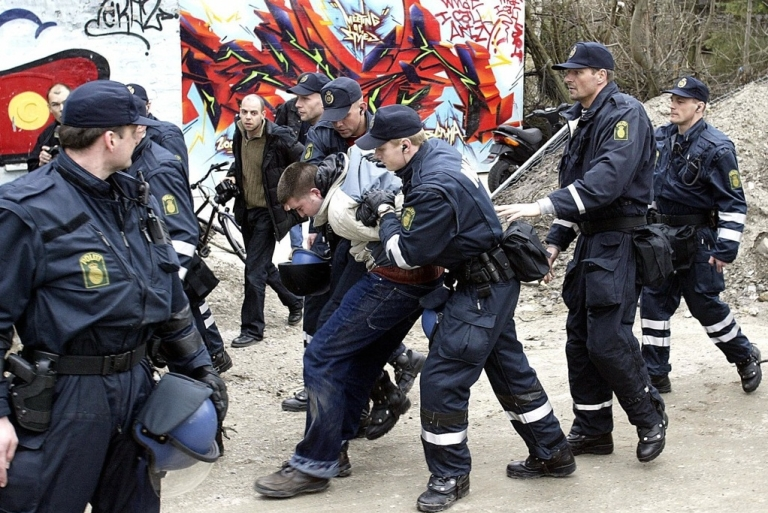 <p>Danish police arrest an unidentified person in a raid in Copenhagen's Free City, Christiania, in 2004 in a final attempt to close down the world famous Pusher Street. These days, the city is taking an increasingly libertarian approach.</p>