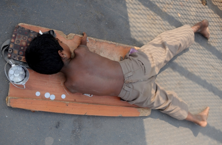 <p>A handicapped child lies on a mat while begging for alms next to a few  Indian rupee and paise coins given to him in Mumbai on December 7, 2011. Rarely considered for conventional employment, there are few options for the disabled in India.</p>