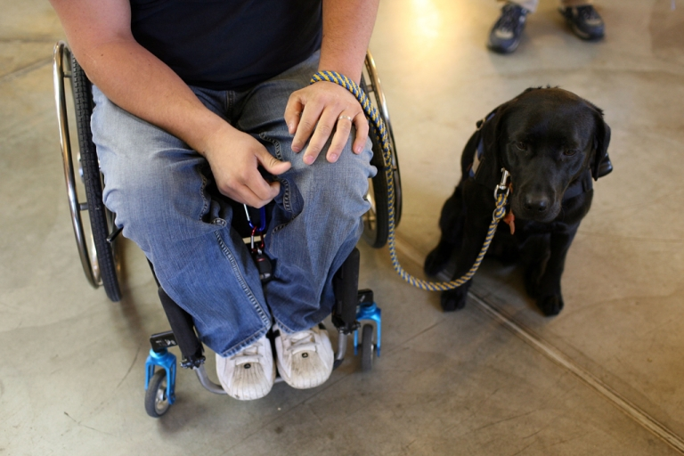 <p>Andrew Pike, a veteran of the U.S. Army 82nd Airborne who was shot and paralyzed during the Iraq war, sits with his new service dog