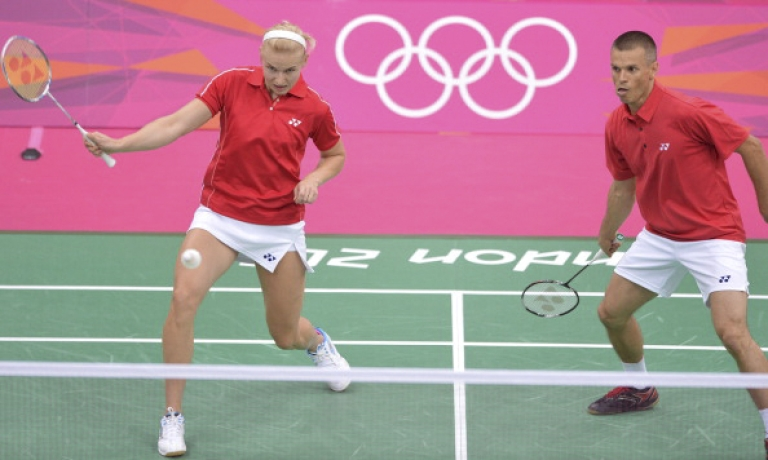 <p>Nadiezda Zieba of Poland (L) is watched by her partner Robert Mateusiak of Poland as she plays a stroke during their badminton mixed doubles group match against Shintaro Ikeda and Reiko Shiota of Japan at The London 2012 Olympic Games in London on July 28, 2012. Poland's Robert Mateusiak and Nadiezda Zieba won 21-8, 22-20.</p>