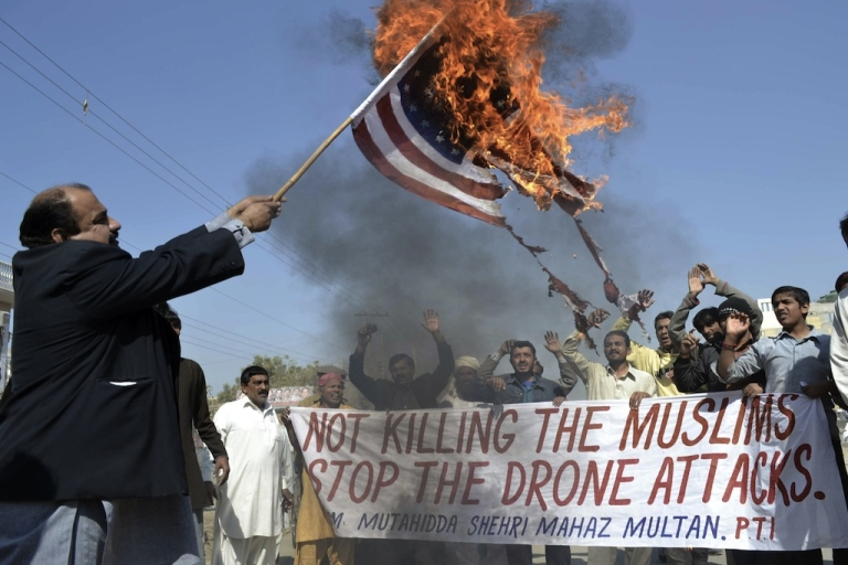 <p>A Pakistani protester holds a burning US flag as they shout slogans during a protest in Multan on February 9, 2012 against the US drone attacks. Thousands have been killed by drones since 2004, many believed to be civilians.</p>
