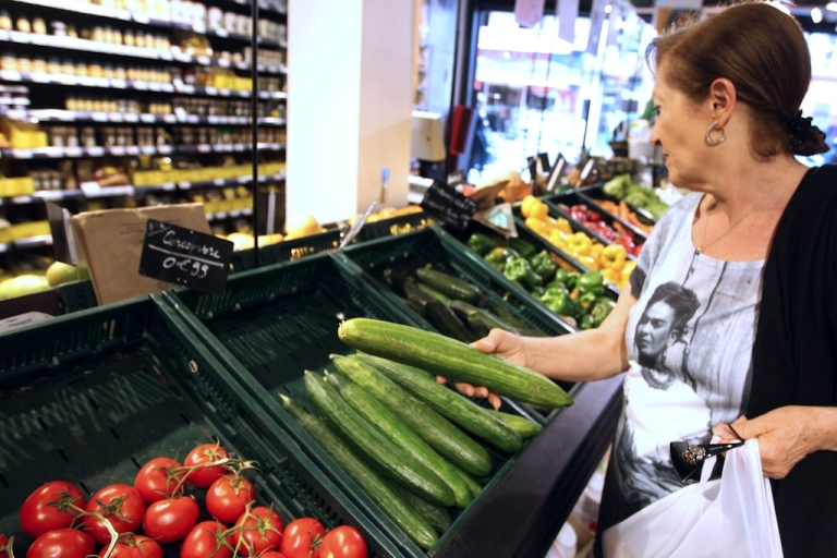 <p>A woman picks up a cucumber from a vegetable stall on May 30, 2011, in a supermarket in Paris.</p>
