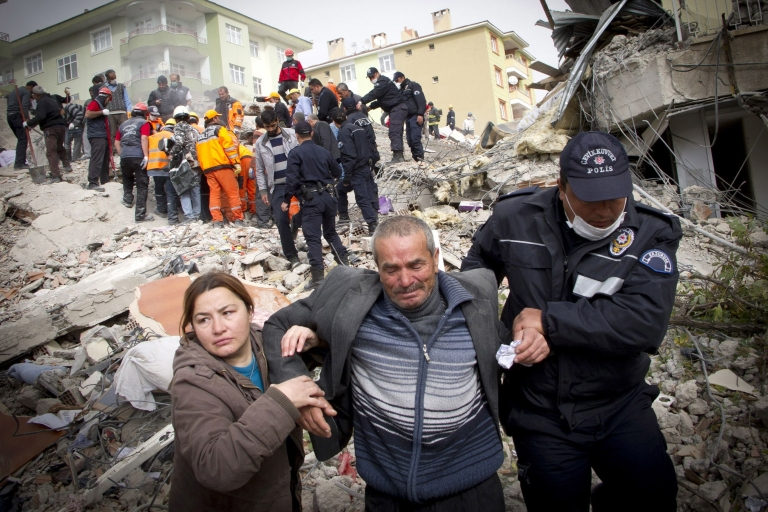 <p>Relatives of victims cry on the ruins after an earthquake in Ercis province of Van, in Turkey, on Oct. 25, 2011.</p>