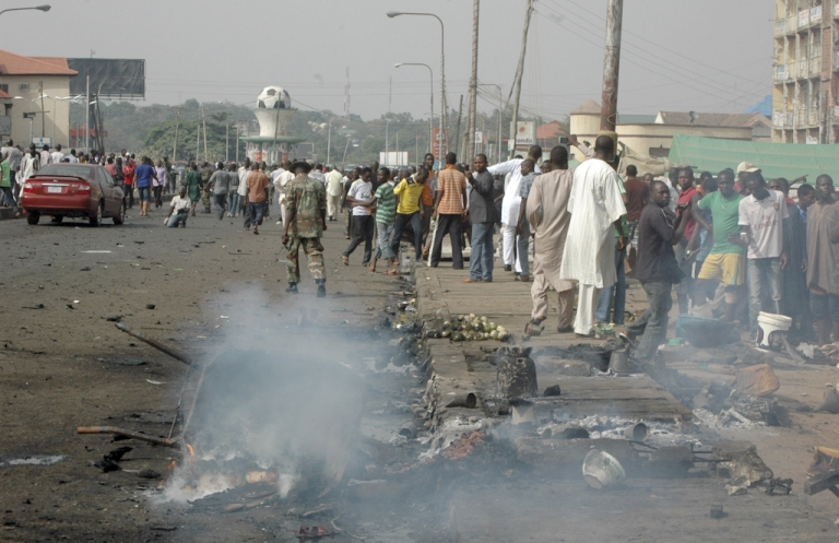 <p>Soldiers chase away onlookers at the scene of the blast off the street in northern Nigerian city of Kaduna on April 8, 2012 after a car explosion killed at least 38 people, most of them commercial motorcyclists near a church. The explosion, a stark reminder of Christmas Day attacks that left dozens of people dead in Africa's most populous nation and largest oil producer, hit the city of Kaduna, a major cultural and economic centre in the north. Motorcycle taxi drivers and passers by appeared to have borne the brunt of the blast, and body parts littered the area.</p>