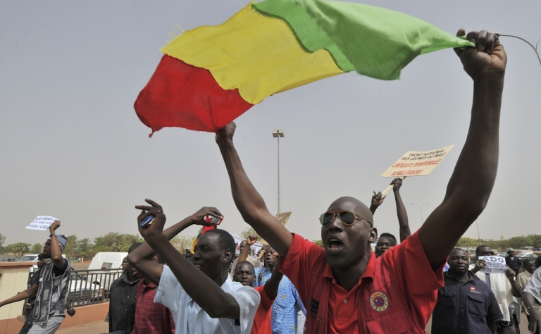 <p>Malian military junta supporters gesture at the airport in Bamako, Mali's capital, on March 29, 2012. A bid by west African leaders to seek a return to democratic rule in Mali fell apart Thursday when the team turned back mid-air after a pro-coup demonstration in Bamako airport.</p>