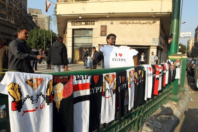 <p>A street vendor displays t-shirts on March 27, 2011 in Cairo's Tahrir Square.</p>