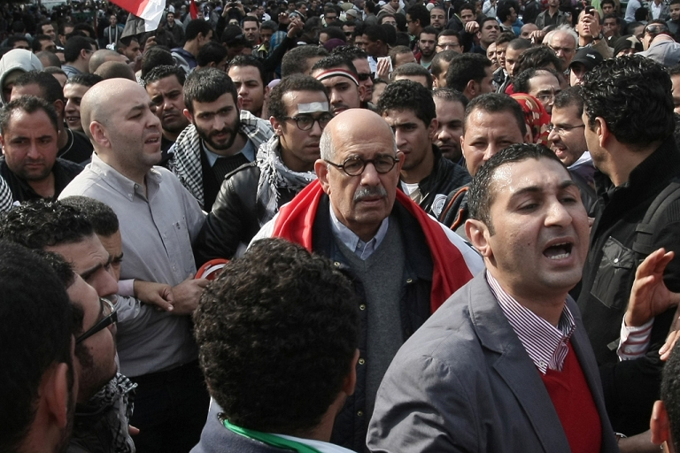 <p>Mohamed ElBaradei (C), with a national flag around his shoulders, among thousands of protesters in Cairo's Tahrir Square on Nov. 25, 2011.</p>