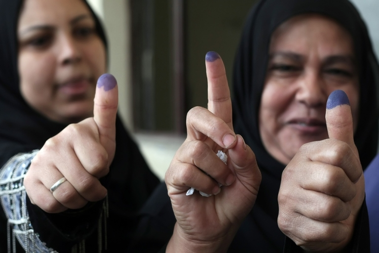 <p>Egyptian women show their ink-stained fingers at a polling station in Cairo on Nov. 29, 2011.</p>