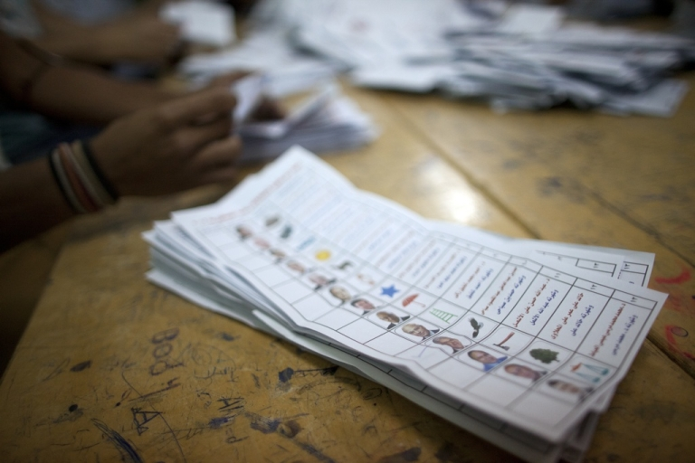 <p>An Egyptian election official counts ballot papers at a polling station in Cairo on May 24, 2012 after polls closed in the country's landmark presidential election.</p>