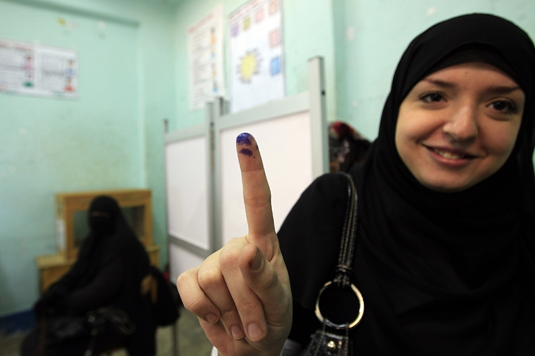 <p>An Egyptian woman shows her ink-stained finger after she voted at a polling station in Giza district near Cairo on December 21, 2011 in the run-off of the second round of legislative election marred by deadly clashes between protesters and security forces.</p>