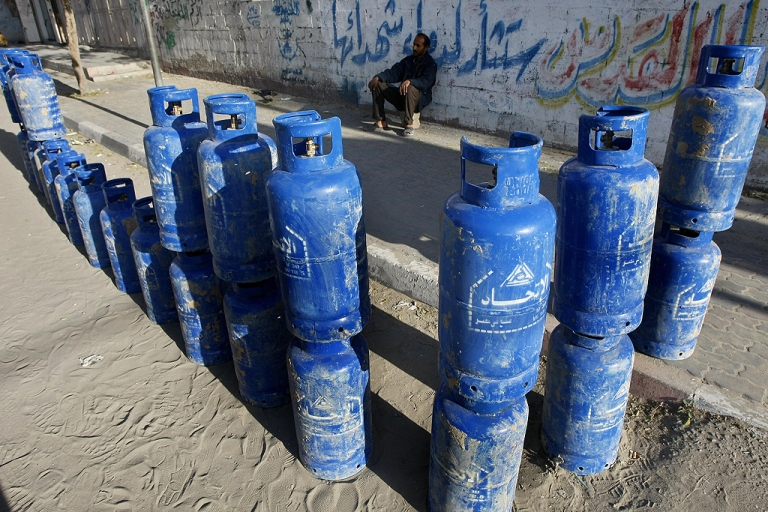 <p>A Palestinian man sits with cylinders of cooking gas, smuggled into the Gaza Strip from Egypt through a tunnel, that he is selling on a street in Gaza city on December 6, 2008.</p>