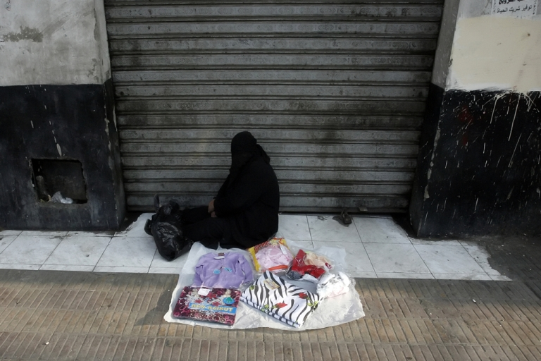 <p>An Egyptian woman sells clothes on the side of a road in Cairo. Some 40 percent of Egyptians live on less than $2 per day, the World Bank says.</p>
