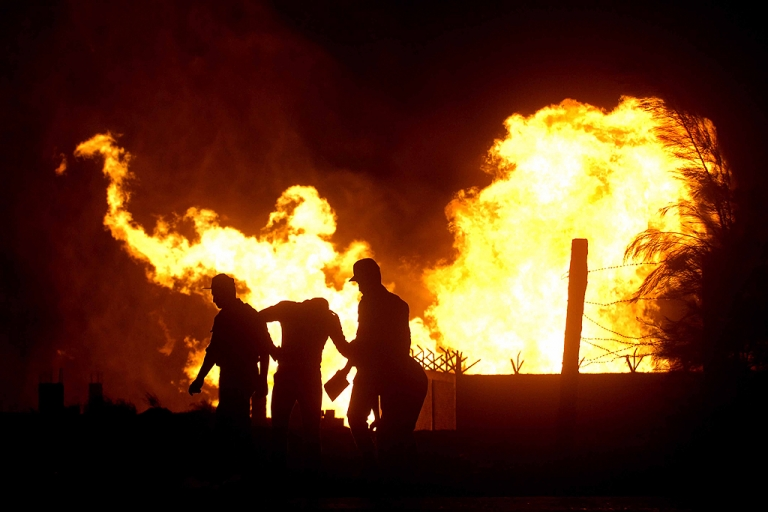 <p>Egyptian security stand in the vicinity of flames following an attack by saboteurs on an Egyptian gas pipeline on July 12, 2011, at al-Arish in the north of the Sinai peninsula.</p>