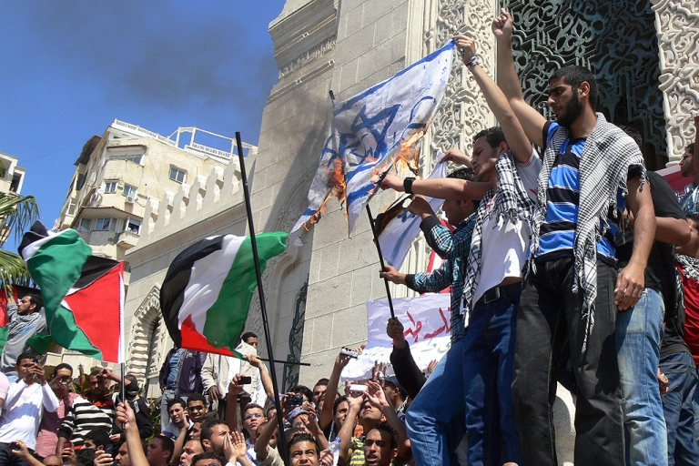 <p>Protesters hold up the Palestinian flag as they burn the Israeli flag during a rally to mark the 1948 creation of the Jewish state known in Arabic as the