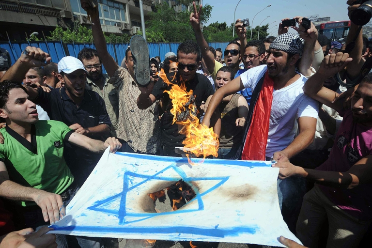 <p>Egyptians burn an Israeli flag during a demonstration outside the Israeli embassy in Cairo on August 19, 2011 after Egyptian policemen were killed on the border with Israel the day before as Israeli troops pursued militants behind a deadly attack.</p>