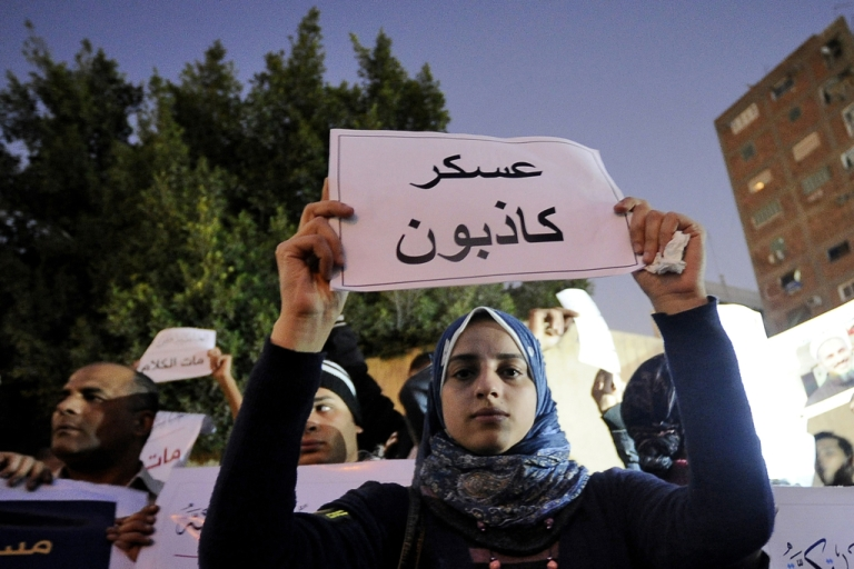 <p>An Egyptian protester holds a sign reading 'Soldiers are liars' during a demonstration against the country's military rulers in Cairo's Abbassiya district. Activists are now using