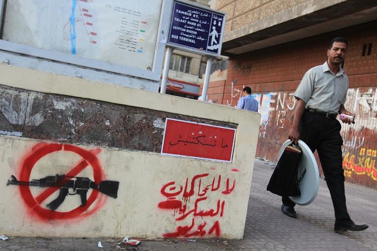 <p>An Egyptian man walks past an Arabic slogan that reads,