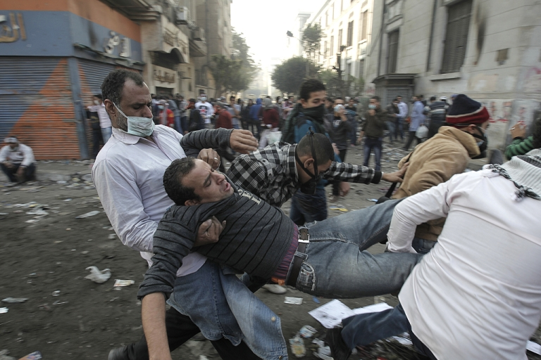 <p>An Egyptian protester is carried away during clashes with riot police along a road which leads to the Interior Ministry, near Tahrir Square, in Cairo on November 23, 2011.  Several thousand Egyptians rallied in Tahrir Square demanding an end to military rule, despite a promise by the country's interim leader to transfer power to an elected president by mid-2012.</p>