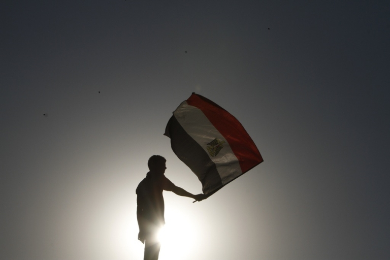 <p>An Egyptian protester waves the national flag in Cairo's landmark Tahrir Square on June 5, 2012.</p>