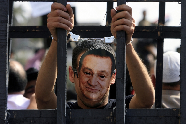 <p>An Egyptian protester wearing the mask of ousted Egyptian president Hosni Mubarak stands with handcuffs inside a makeshift prison cell at Cairo's Tahrir Square on April 8, 2011 during a demonstration attended by tens of thousands of Egyptians, two months after Mubarak was ousted, to demand that former regime officials including the veteran strongman be purged and tried.</p>