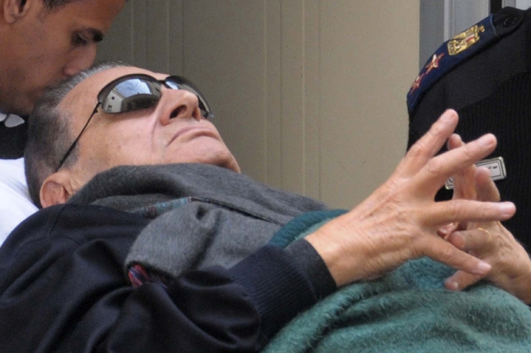 <p>Former Egyptian president Hosni Mubarak, lies on a stretcher as he leaves court following his trial at police academy, on the outskirts of Cairo on January 2, 2012.</p>