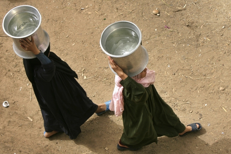 <p>Egyptian women walk with containers filled with water in al-Rahawe village, outside of Cairo, on May 27, 2010. Thousands of Egyptians living just a stone's throw from the Nile suffer supply and sanitation problems.</p>