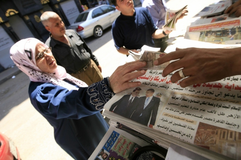 <p>An Egyptian woman buys a newspaper featuring a front page picture of US President Barack Obama.</p>
