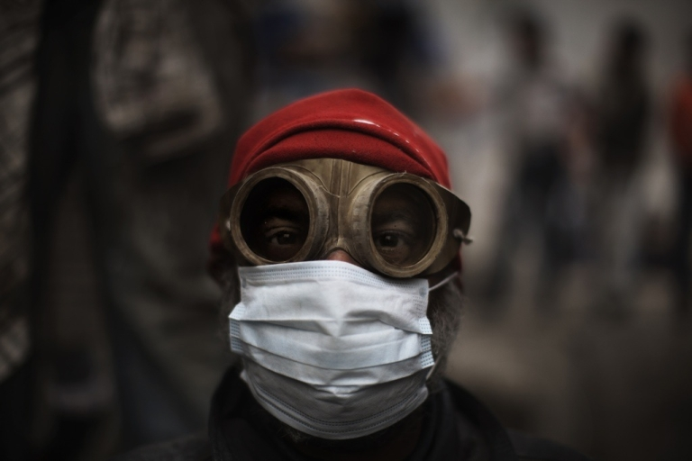 <p>A protester in Cairo, Egypt uses goggles and a protective mask against tear gas fired by riot police during confrontations outside Cairo's security headquarters on Feb. 6, 2012.</p>