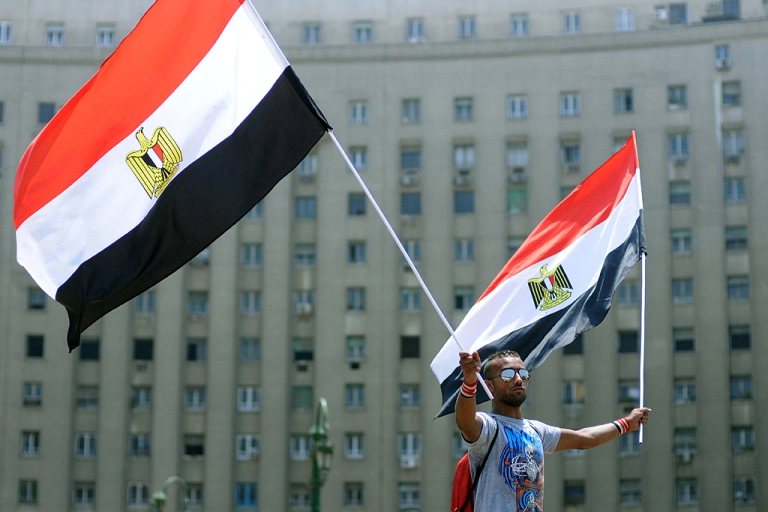 <p>An Egyptian man waves two national flags during a protest in Cairo's Tahrir Square July 11, 2011, vowing to keep up their sit-in which began on July 8, despite a series of concessions by the Egyptian prime minister.</p>