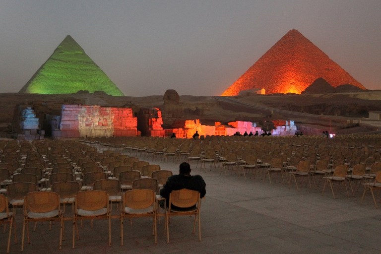 <p>An Egyptian visitor watches a nearly empty light and sound show at the Giza pyramids on February 15, 2011 in Giza, Egypt. With tourism counting for 6 percent of Egypt's gross domestic product, the country's economy has taken a huge hit after foreign tourists fled during Egypt's uprising.</p>
