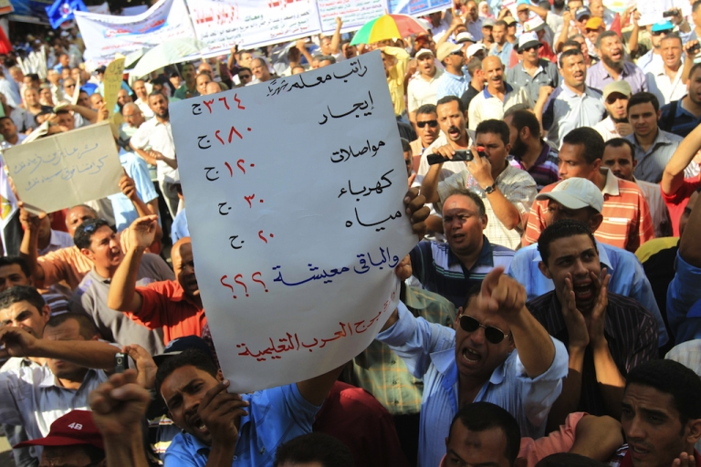 <p>Holding up a sign listing the cost of living, thousands of the Egyptians teachers protest during a strike in front of the Prime Minister's office in downtown Cairo in Sep. 2011. Tomorrow, dozens of groups and universities will begin an open strike against the military-run government.</p>